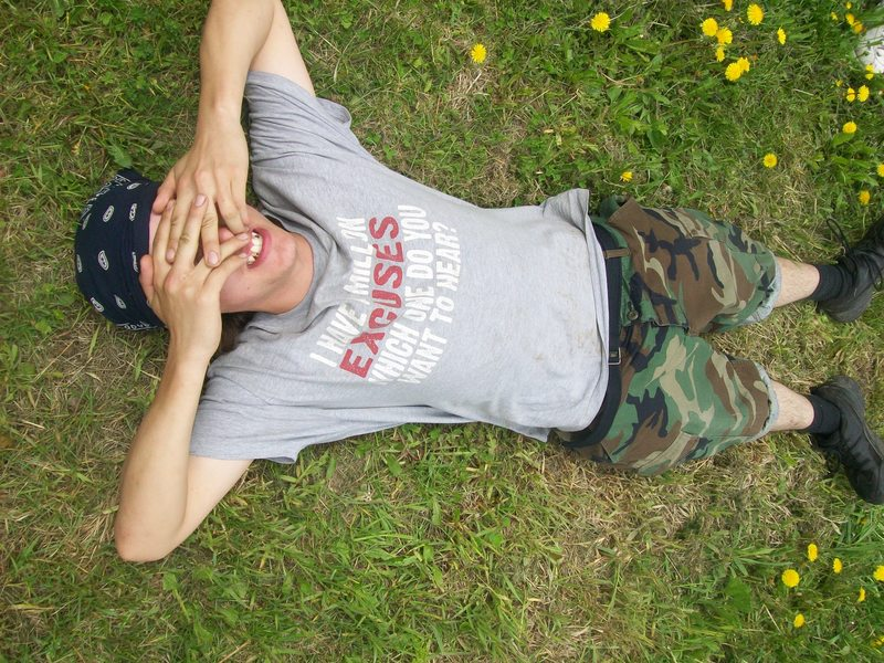 A student laying in the grass with his hands over his face, exhausted from an attempt at climbing a fire tower.